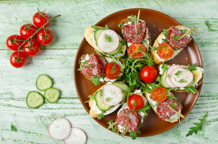 appetizers: Fresh toast sandwiches with cottage cheese, egg, radish, cucumber, salami, cherry tomatoes and arugula