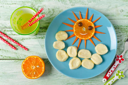 ni�os desayunando: Children breakfast lazy dumplings and orange in the shape of the funny face sun. Lazy dumplings of cottage cheese at blue plate Foto de archivo