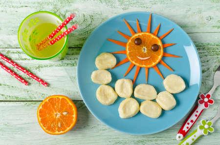 perezoso: Los niños el desayuno albóndigas perezosos y naranja en la forma de la cara divertida sol. albóndigas de descanso de requesón en la placa azul Foto de archivo