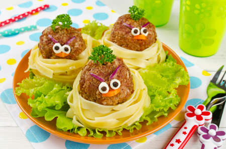 Funny spaghetti with meatballs for kids. Birds in nests Stock Photo