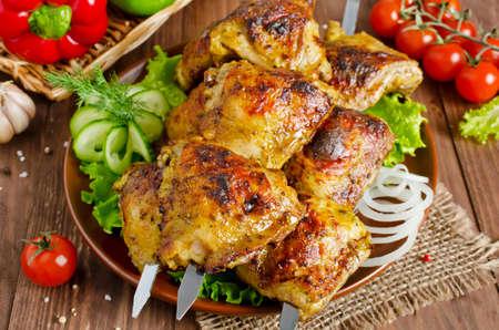 muslos: La parrilla de muslos de pollo en los pinchos con verduras Foto de archivo