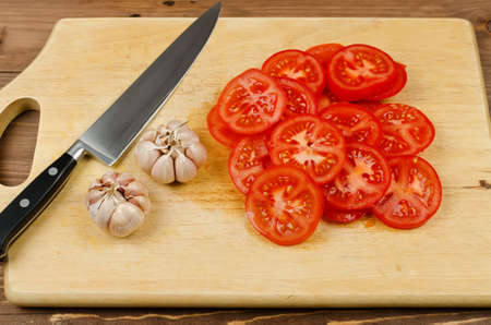 tomato slices: Red tomato slices, garlic and knife on chopping board. Preparation of vegetables on a wooden table
