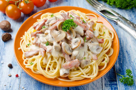 Spaghetti with Bechamel sauce, mushrooms and bacon on a wooden table