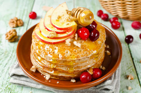 honey apple: Homemade pancakes with honey, apple, cranberries and nuts. A stack of pancakes on a wooden table Stock Photo