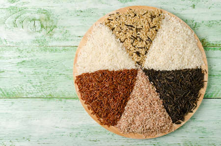 Various varieties of rice on a wooden table. Rice is an important source of several B vitamins, minerals and complex carbohydrates.