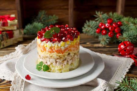 Gelaagde salade van groenten op de vakantie tafel. Salade met walnoten, kaas, granaatappel en groenten