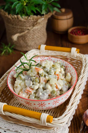 Russian traditional salad Olivier with vegetables and meat. Winter salad