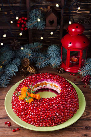Salad Garnet bracelet on the holiday table. Vegetable salad with pomegranate seeds