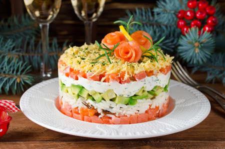 Gelaagde salade met zalm, avocado en roomkaas. Salade voor de vakantietafel