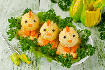 Funny chickens from eggs on the Easter table. Snack of cheese and almonds Stock Photo