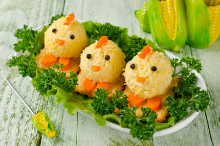aliments droles: Funny chickens from eggs on the Easter table. Snack of cheese and almonds Banque d'images