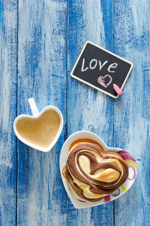 desayuno romantico: Sweet chocolate buns with coffee on the table. Romantic breakfast
