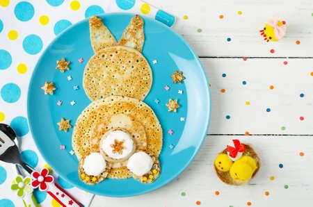 Grappige konijntjespannekoeken op de plaat. Creatief ontbijt voor kinderen. Bovenaanzicht Stockfoto