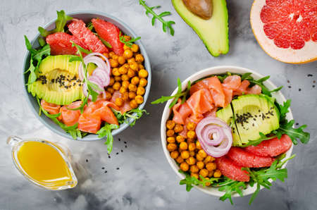 Healthy salad bowl with salmon, grapefruit, spicy chickpeas, avocado, red onion and arugula. Delicious balanced food concept