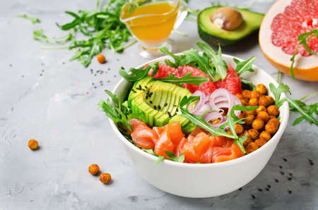 Ensaladera saludable con salmón, pomelo, garbanzos picantes, aguacate, cebolla roja y rúcula. Delicioso concepto de comida equilibrada