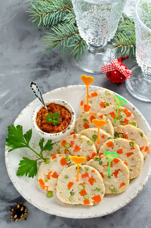 Fish roll (roulade) with green peas and carrots. New years appetizer