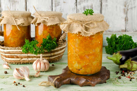 Eggplant caviar in a glass jar on a wooden table. Homemade canning winter preserve Stock Photo