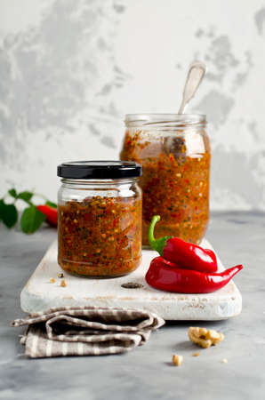 Homemade sauce adjika with hot pepper, garlic, basil, parsley and walnuts. Tabasco Archivio Fotografico