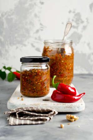 Zelfgemaakte saus adjika met hete peper, knoflook, basilicum, peterselie en walnoten. tabasco Stockfoto