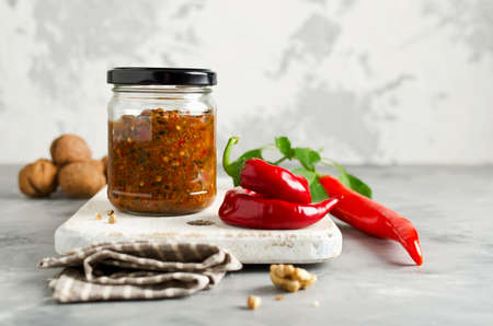 Homemade sauce adjika with hot pepper, garlic, basil, parsley and walnuts. Tabasco