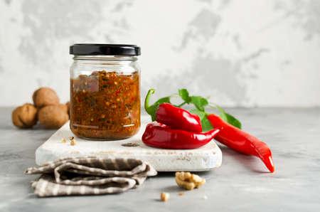 Zelfgemaakte saus adjika met hete peper, knoflook, basilicum, peterselie en walnoten. tabasco