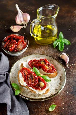 Bruschetta z oliwą, suszonymi pomidorami, twarogiem i świeżą bazylią. Smaczne pikantne włoskie przekąski