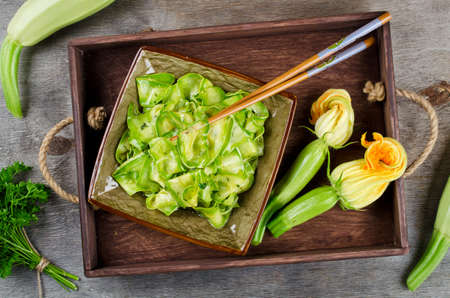Zucchini ribbon salad with parsley, dill and garlic in marinade. Vegetarian cuisine
