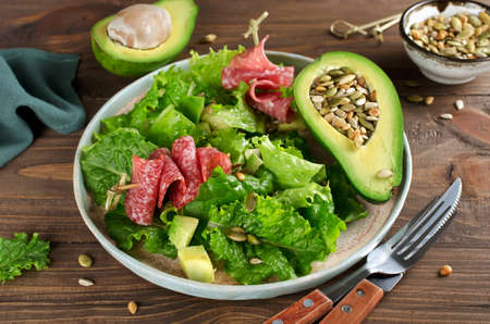 Salad with avocado, salami, pine nuts, pumpkin seeds and sunflower seeds. The concept of healthy food