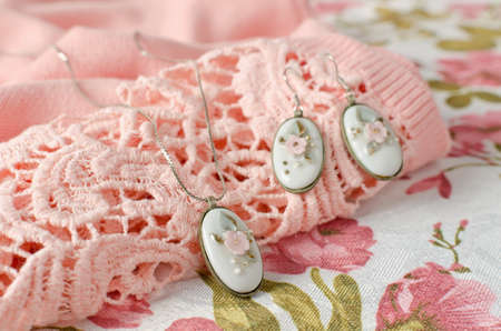 Earrings and pendant on a chain with an oval-shaped brass frame with a porcelain cabochon insert. Vintage decoration