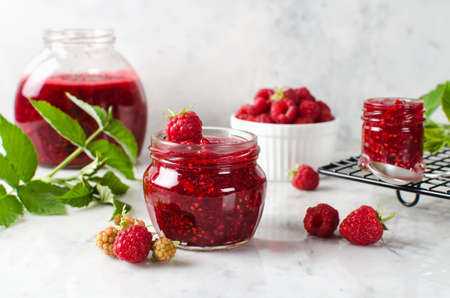 Homemade jam made from ground raspberries and sugar. Jam in a jar on a marble table