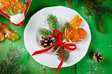 Lollipop in shape of rooster on the stick on Christmas background. Traditional Russian candy caramel
