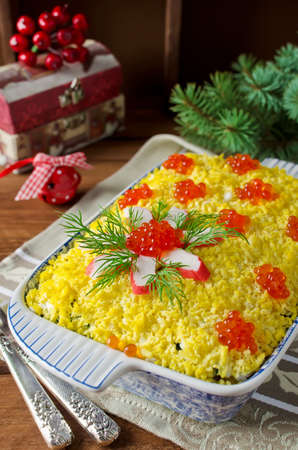 Salad with crab sticks, corn, cucumber, and rice decorated with red caviar
