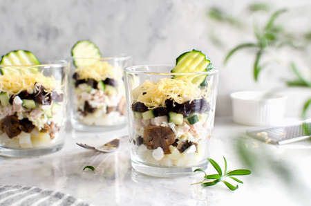Layered salad with chicken, mushrooms, prunes, eggs, cucumbers, potatoes and cheese. Salad in a glass on a marble background