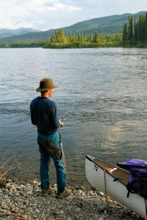 yukon territory: Man fishing on Yukon river in Canada Stock Photo