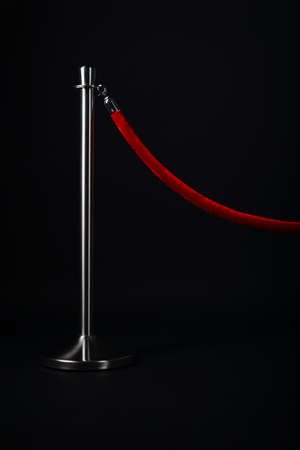 silver stanchion with a red rope, isolated on black Stock Photo - 16892122