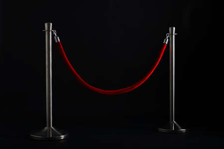 silver stanchions with a red rope, isolated on black