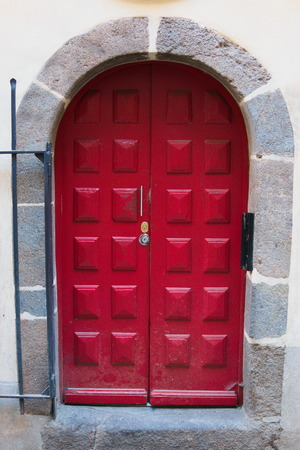 Beautiful red door with stone entryway and steel gate Stock Photo