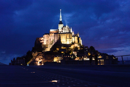 Mont Saint Michel at night long exposure centered view lit up clouds in sky dark high contrast Archivio Fotografico