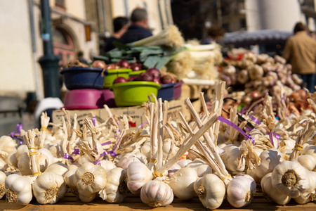 Bunches of garlic for sale at farmers market street scene with people in the background close up 版權商用圖片