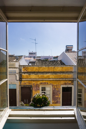 Hotel window view looking out to Faro, Portugal street scene southern european architecture
