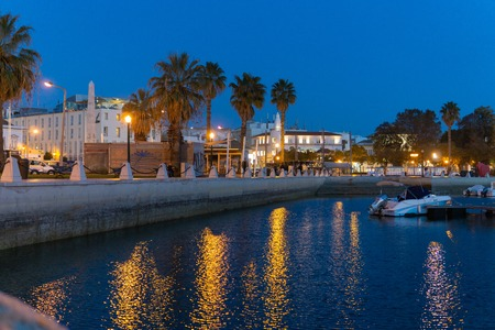 Faro Portugal marina night scene boats palm trees and buildings lit up