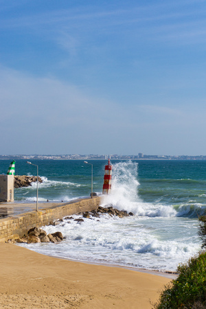 Wave splashes against lighthouse in Lagos, Portugal