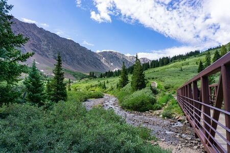 Beautiful alpine scene with bridge over stream leading to Gray's Peak, Colorado