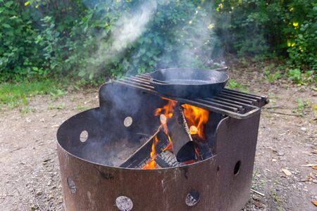 Cast iron skillet warming over bonfire camping cooking Imagens