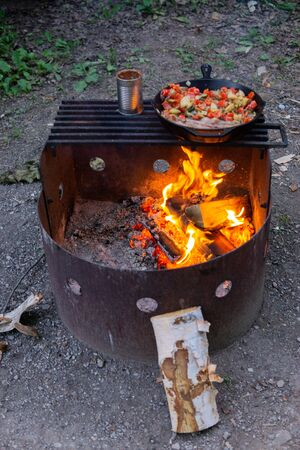 Summertime camp meal cast iron skillet bacon beans and potatoes Banco de Imagens