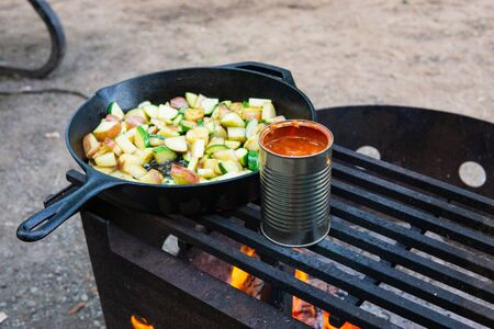 Cooking veggies and beans over campfire rustic camping