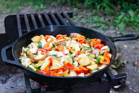 Dinner cooking over the fire on cast iron pan rustic camping