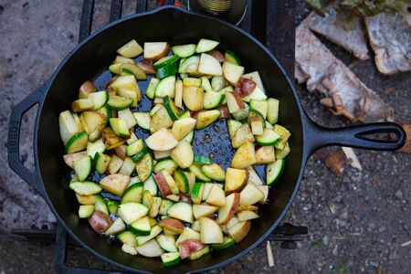 Close up cooking in cast iron skillet over campfire potatoes veggie mix