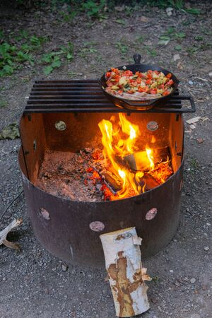 Dinner cooking over open fire cast iron skillet camping bacon and vegetables