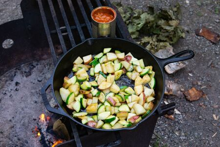 Cooking dinner over camp fire camping rustic meal potatoes onions zucchini vegetables Banco de Imagens